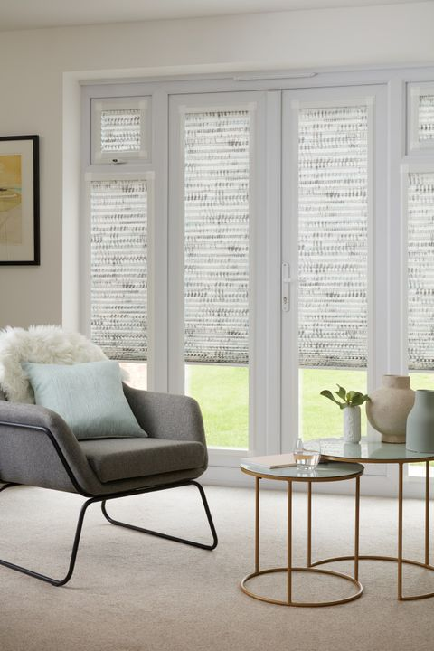 Duo natural Thermashade Perfect Fit Pleated blinds from House Beautiful range dressed on bifold doors of living room with smalll round table and grey chair with cushions.