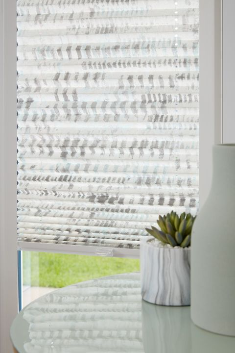 Close up of duo natural Thermashade Perfect Fit Pleated blinds dressed on bifold doors of living room.