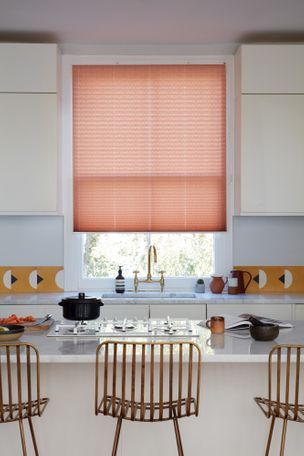 Peach pleated blinds dressed on the windows of white painted kitchen.