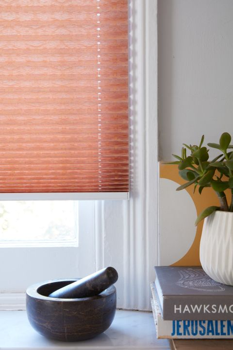 Close up of peach Pleated blinds dressed on the windows of white painted kitchen.