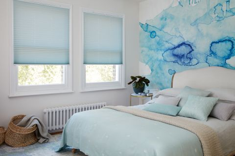 Light blue Pleated blinds dressed on windows of white painted bedroom with feature wall having abstract blue design.