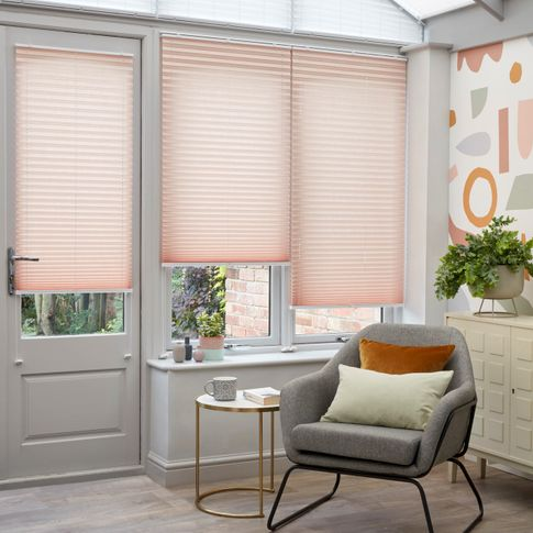 Peachy pink Pleated blinds hanging at varying drop heights on the conservatory doors and windows and upper windows are dressed with white Highgrove pleated blinds.
