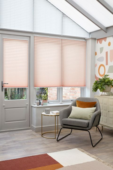 Peachy pink Pleated blinds hanging on the conservatory doors and windows. A grey chair and coloured cushions are also in the room.