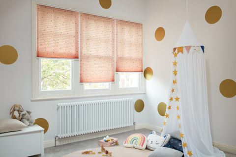 Gold dot-print on a pale pink/peach Pleated blinds dressed on windows of kids' room.