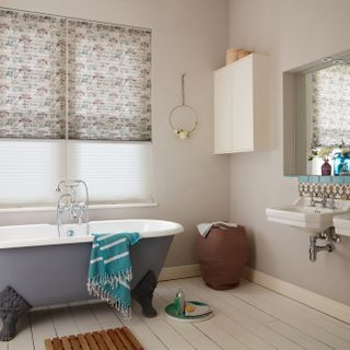 Light grey Transition Pleated blinds featuring some trees printed with blue and purple dots dressed on windows in the bathroom.  A blue-grey bath is placed in the bathroom.