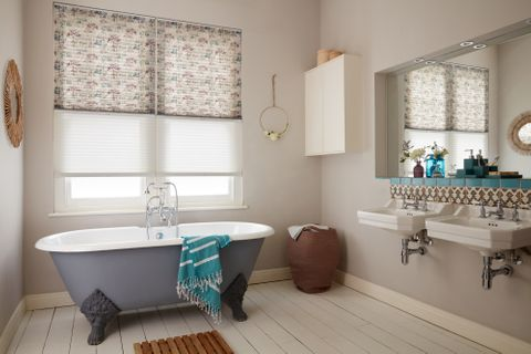 Transition Pleated blinds with printed dot-tree pattern and a sheer white blind dressed on windows in the bathroom.  A grey bath is placed in the bathroom.