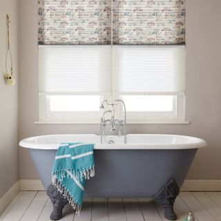 Transition blinds in sheer white and tree patterns in blue and plum at window, above a blue rolltop bath.