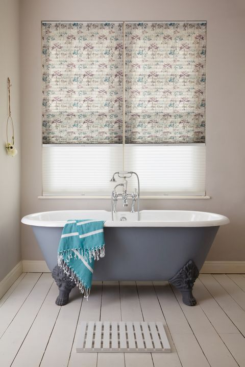 Transition blinds in sheer white and neutral with tree patterns in blue and plum at window, above a blue rolltop bath with a blue striped towel.