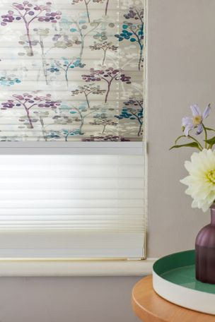 Close up of light grey Transition Pleated binds featuring some trees printed with dots in turquoise or purple on top blind and sheer white blind underneath.