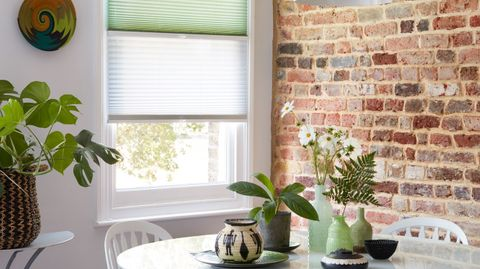 Mint green and sheer white Transition Pleated blinds dressed on the window in dining room.