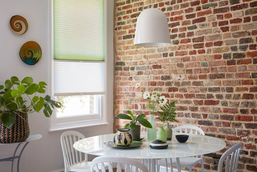 Mint green and white Transition Pleated blinds dressed on the window in dining room with white bistro table and chairs.