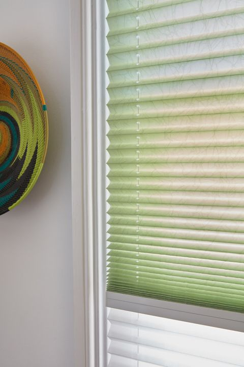 Close up of mint green and white Transition Pleated blinds dressed on the window in dining room.