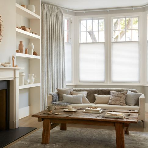 White curtains featuring light grey pattern on curtains dressed over cafe style Pleated blinds on windows of living room.