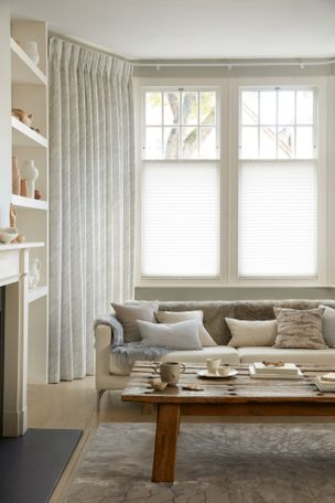 Corner view of a living room where white curtains featuring light grey pattern on curtains dressed over cafe style Pleated blinds on windows.
