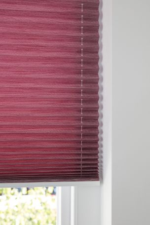 Close up of maroon Pleated blinds dressed on a window.