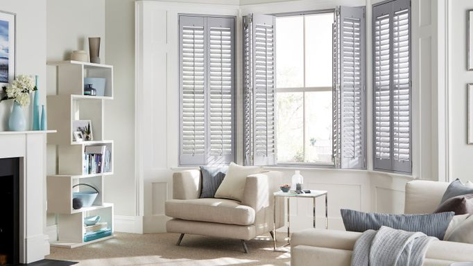 Grey full height shutters from housebeautiful range dressed on windows of cream living room. Cream sofa chairs can also be seen in the view.