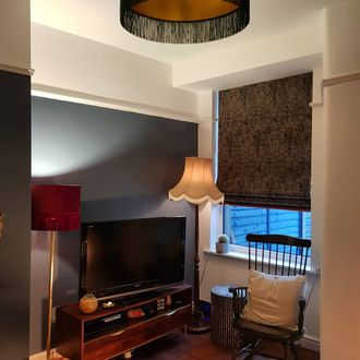 Dark grey textured roman blinds dressed on window in living room
