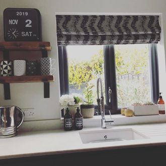 Fade-out black and white wavy line zig-zag printed roman blinds hanging on windows in kitchen