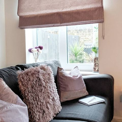 Grey sofa with pink cusions and fluffy pink cushion window featuring pink roman blind