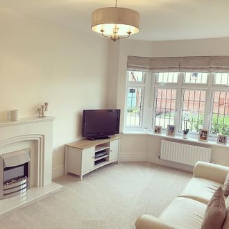 Living room, white walls, cream sofa windows featuring grey roman blinds