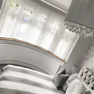 Shoot from an angle of bedroom featuring white wooden blinds on windows. Bed is covered with white and grey striped duvet and matching plain grey, plain white and striped cushions and pillows.