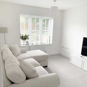 White wooden blinds hanging on the windows of white painted living room.  Cream sofa has been placed in the room.