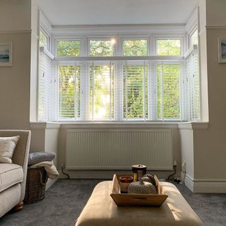 Living room with cream walls and sofas featuring bay window with white wooden veneitan blinds