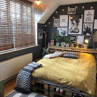 Boys bedroom with yellow bedding, dark walls filled with black and white pictures featuring dark wooden venetian blinds with tape