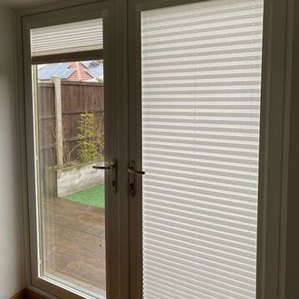 Focus on patio door featuring white perfect fit pleated blinds
