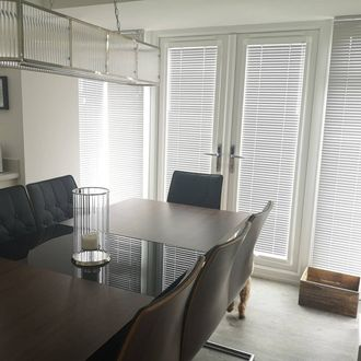 angled shot of dining room showing perfect fit window blind of silver venetian blinds