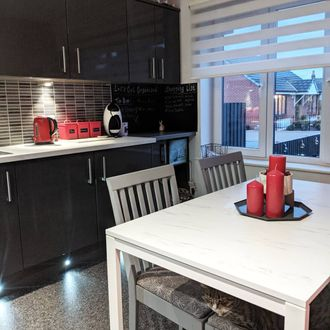 Black and white kitchen with a white dining table with red accesories, featuring a white day & night blind