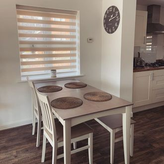 Kitchen space with dining table rustic modern style, window findow day and night blinds in a cream colour