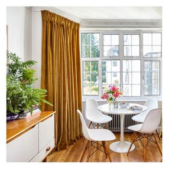Corner shot from both sides of dinging room living area, modern white dining table, window featuring ochre velvet curtains