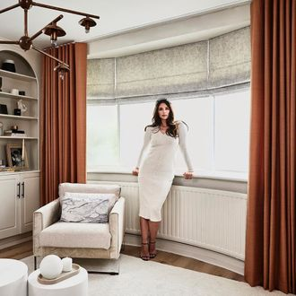 Front shot from living room- windows featuring Cinnamon coloured curtains, layered over a grey roman blind and white sheer roller blinds