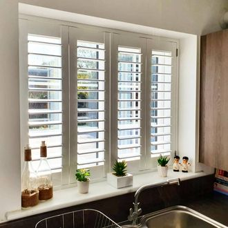 Front picure of new kitchen white shutters intalled in window