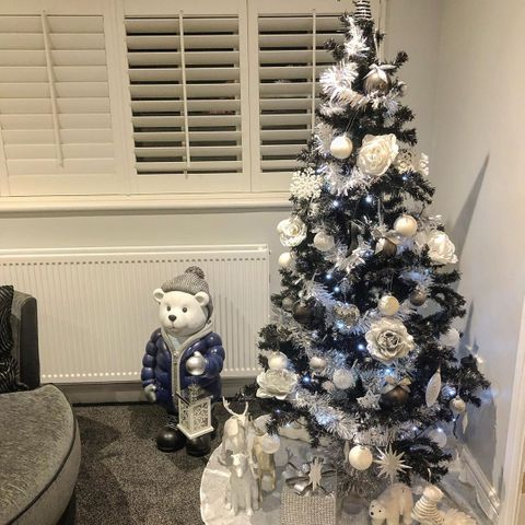 Corner shot featuring white and silver decorated christmas tree with white shuttesr in the window