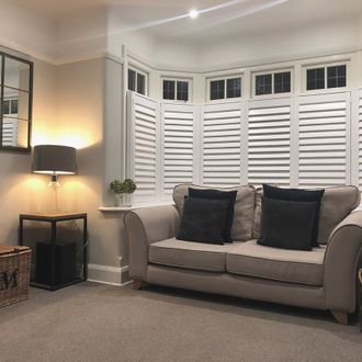 Living room shot, grey sofa, dark grey cushions and window feature white shutters
