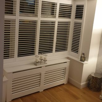 Front picure of new bay white shutters intalled in window