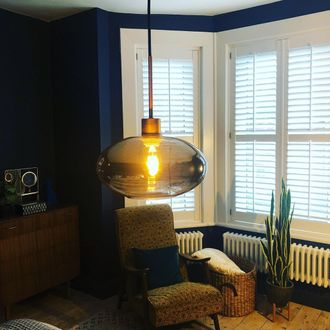 Drak navy walls, mid century trend, wooden units, cactus plants and featuring white shutters in a bay window