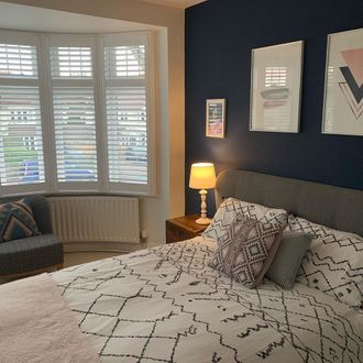 Bedroom shot, white patterned sheets, pink throw and dark blue walls featuring bay window white shutters