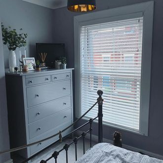Bedroom corner shot, grey chester drawers featuring white wooden blinds