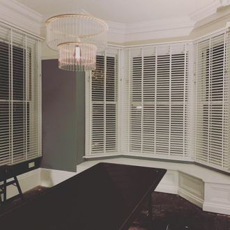 Front on bay window shot in dining room of white wooden venetian blinds