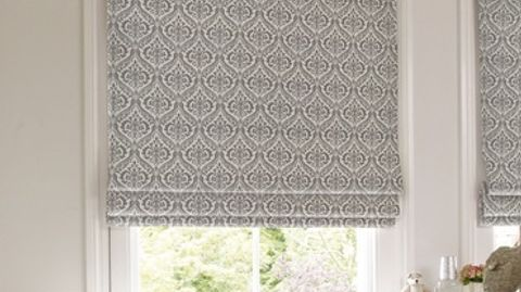 Silver and white roman blind designed with a repeating pattern is fitted to a rectangular window in a room decorated in white