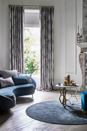 Grey patterned silky look curtains dressed over grey roman blinds over window in a living room