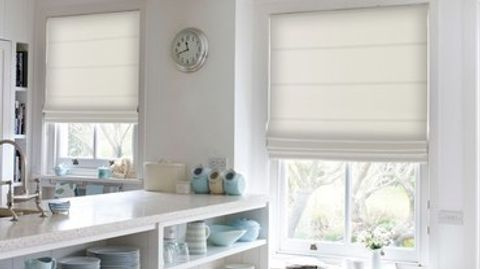 Ivory coloured roman blinds attached to rectangular windows in a kitchen decorated in white with marble countertops