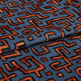 Grey background and orange embrodiered folded fabric in living etc