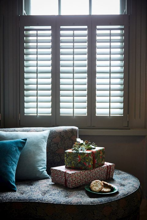 grey cafe style shutters in a conservatory setting with a sofa covered in cushions in front
