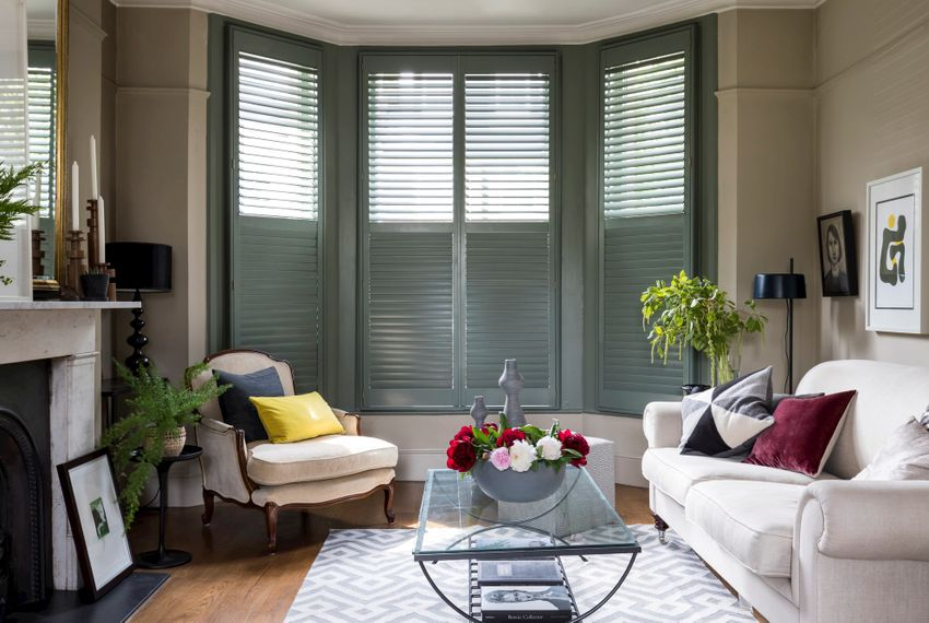 green custom colour full height shutters in living room with cream sofas