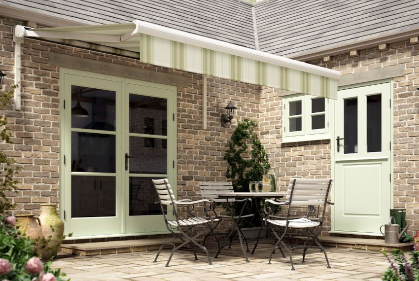 Beige and green striped awnings installed on a wall with patio doors. Garden table and chairs are placed under awnings