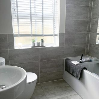 Wooden blinds dressed on window of bathroom , walls decorated with grey tiles